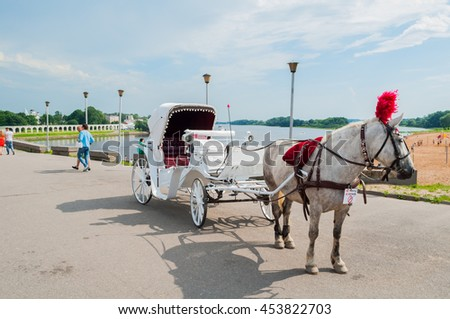 VELIKY NOVGOROD, RUSSIA - JULY 15, 2016. Pleasure horses crew - horses in harness with elegant carriage on the background of Yaroslav's Courtyard in sunny day in Veliky Novgorod, Russia