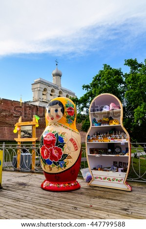 VELIKY NOVGOROD, RUSSIA -JUNE 11, 2016. Belfry of St Sophia cathedral with big colorful Russian doll matrioshka on the foreground and souvenir trade in Veliky Novgorod, Russia