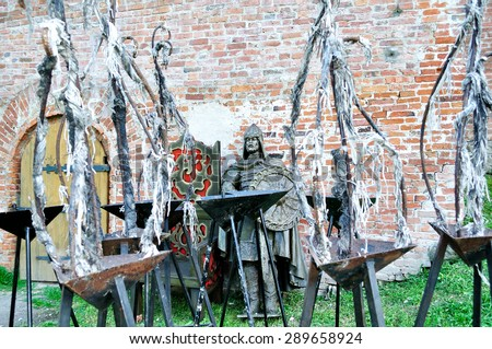 VELIKY NOVGOROD, RUSSIA - JUNE 2, 2015. Metal figure of ancient Varangian druzhinnik (member af ancient Slavic prince's squad) next to the Prince throne and tripods to keep the fire on the foreground