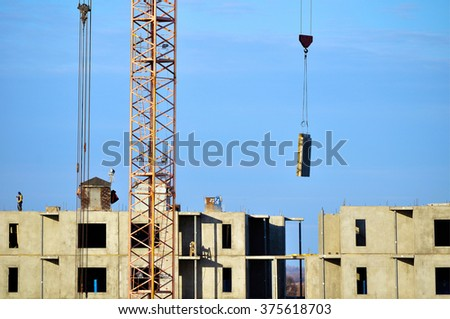 VELIKY NOVGOROD, RUSSIA - MARCH 10, 2015.  The movement by crane the concrete slab suspended on building slings. Industrial work at the construction of residential block house.