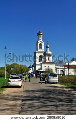 VELIKY NOVGOROD, RUSSIA - MAY 10. 2015.  Architectural ensemble - bell tower and Church of Exaltation of the Cross in Russian orthodox Yuriev Monastery, and parishioners walking along - stock photo