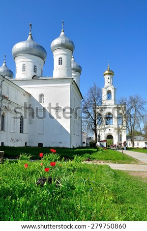 VELIKY NOVGOROD, RUSSIA - MAY 10. 2015.  Saviour Cathedral,  bell tower and tourists walking along on the territory of Russian orthodox  Yuriev Monastery  in spring sunny day - stock photo