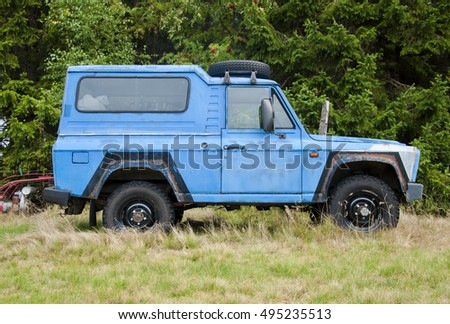 VELKA UPA, THE CZECH REPUBLIC, 07.10.2016 - Blue old rusty SUV Jeep car parking on the meadow. Close up of blue offroad.