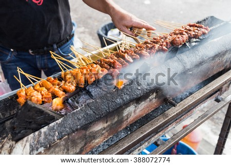 Vendor preparing delicious barbecue chicken and beef satay on charcoal grille with shallow focus on center skewers - stock photo