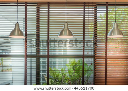 Venetian blinds by the window and ceiling lamp beam - stock photo