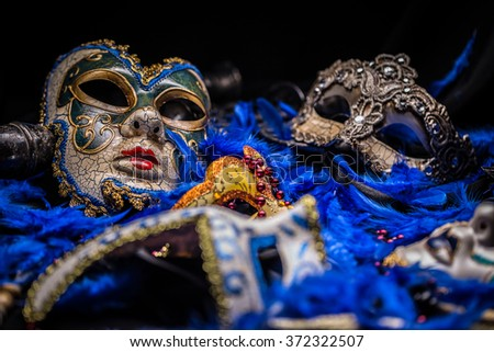 Venetian carnival mask on blue feather background