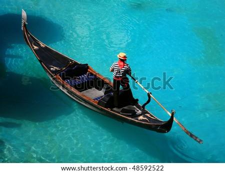 venetian gondola on blue water - stock photo