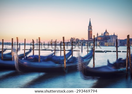 Venetian gondolas and San Giorgio di Maggiore church in background at morning before sunrise, long time exposure, vintage filtered style, Venice (Venezia), Italy, Europe - stock photo
