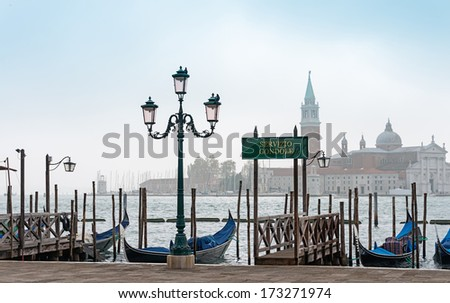 Venetian gondolas on the waterside of lagoon - stock photo
