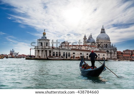 Venetian gondolier punting gondola through green canal waters of Venice Italy - stock photo