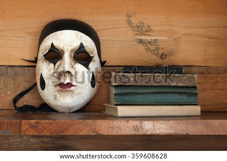 venetian mask and books on a shelf - stock photo