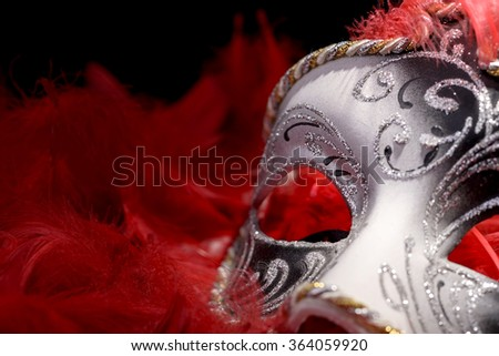 Venetian mask carnival in the midst of red feathers - stock photo
