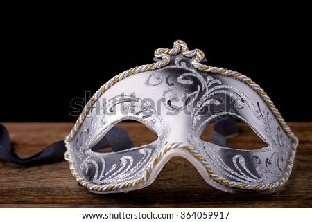 Venetian mask carnival white, black and gold on wood on a black background