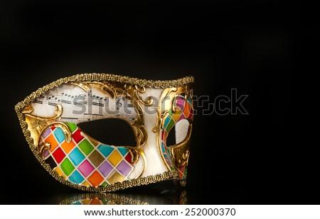 Venetian mask harlequin style isolated on black background. - stock photo