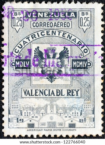 VENEZUELA - CIRCA 1955: A stamp printed in Venezuela issued for the 400th anniversary of Valencia Del Rey city shows emblem and factories, circa 1955. - stock photo