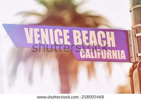 Venice Beach California Street Sign. A street sign marking Venice Beach, California. Backed by a palm tree with a sunset flare. - stock photo