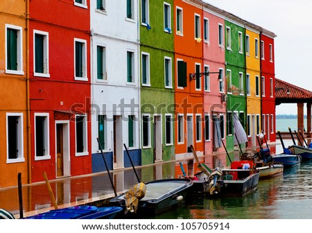 Venice, Burano island canal, small colored houses and the boats - stock photo