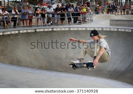 Venice, California, United States - March 16, 2015: A skateboarder in mid-air while performing an Aerial Lip Trick on the Flow Bowl at Venice Skatepark, watched by a group of spectators. - stock photo