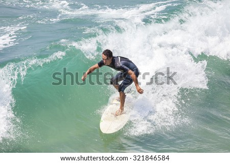 VENICE, CALIFORNIA, USA - AUGUST 22, 2015: Man riding wave at Venice Beach on a beautiful sunny day.