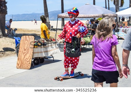 Venice, California, USA - July 12, 2015: A street clown rides a skateboard on the Venice Beach Boardwalk.