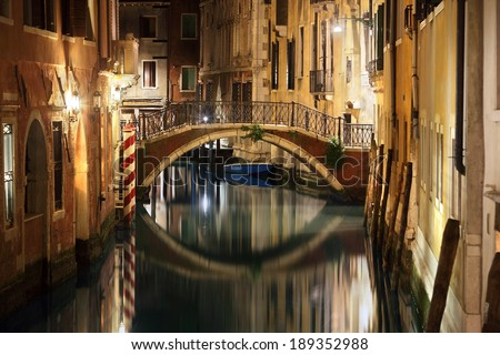 Venice canal late at night with street light illuminating bridge and houses - stock photo