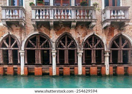 Venice channel and vintage grunge building with columns and arcs  - stock photo