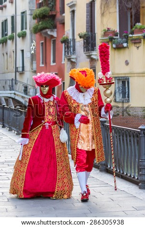 VENICE - FEB 6, 2013: Costumed couple during Venice Carnival. Carnival is an annual festival starting around two weeks before Ash Wednesday and ends on Shrove Tuesday or Mardi Gras - stock photo