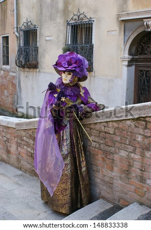 VENICE - FEBRUARY 18: A girl in a purple carnival costume with flowers and a mask is showing her dress on February 18, 2012 in Venice.