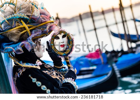 VENICE, FEBRUARY 10: An unidentified woman in typical dress looks into the mirror during traditional Venice Carnival on February 10, 2013 in Venice - stock photo