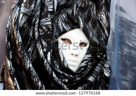 VENICE - FEBRUARY 03 : Unidentified woman with black dress and white mask during celebrations of the Venice Carnival on February 3, 2013.