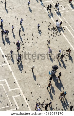 VENICE, ITALY - APR 11, 2007: Tourists on San Marco square feed large flock of pigeons. San Marco square is the largest and most famous square in Venice. - stock photo