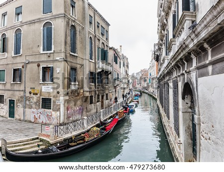 VENICE, ITALY - APRIL 1, 2016: Empty gondolas on a small Venetian canal with a narrow railed street between old shabby buildings.
