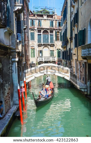 VENICE, ITALY - APRIL 22, 2016: People on a gondola on a canal along classic buildings in the city center
