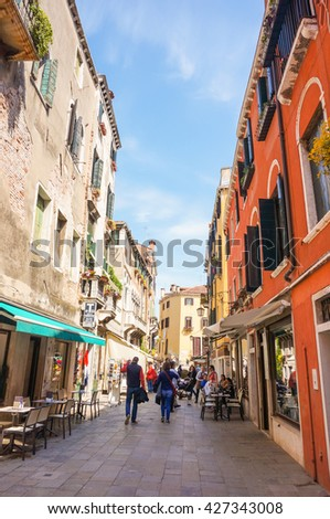 VENICE, ITALY - APRIL 22, 2016: People walking in a street with shops and stores in the shadow - stock photo