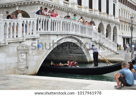 VENICE, ITALY - Aug 14, 2014: Tourists on the bridge watching the gondolas floating on the canal
