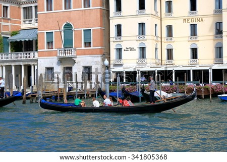 Venice, Italy - August 21, 2015: Sailing in the gondola people by Grand Canal past the Westin Europa & Regina hotel