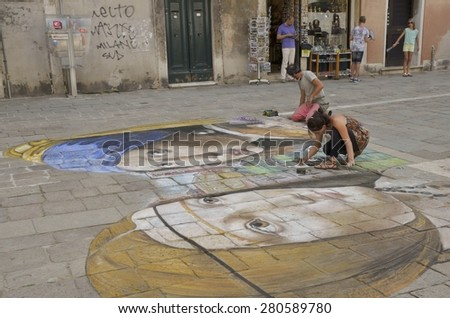 VENICE, ITALY - AUGUST 11: Young street artists drawing on the floor in a square of the district of Santo Polo on August 11, 2014 in Venice, Italy.