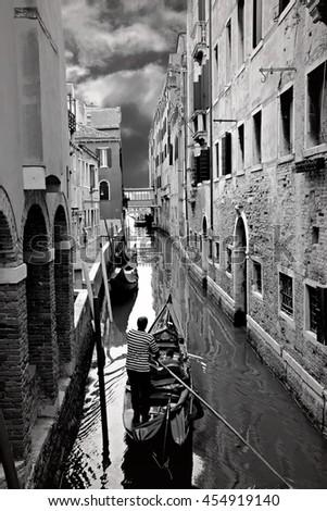 Venice Italy canal with gondola black and white  - stock photo