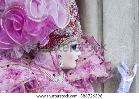 VENICE, ITALY - FEBRUARY 15, 2015:A model disguised with a pink traditional carnival costume, showing her ring during the Carnival of Venice. - stock photo