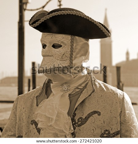 VENICE, ITALY - FEBRUARY 13, 2015: An unidentified masked person in costume Casanova on pier in St. Mark's Square during the Carnival of Venice, Italy. Square sepia toned image. Selective focus. - stock photo