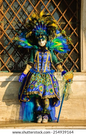 VENICE, ITALY - FEBRUARY 16, 2015: Peacock mask in sunlight near Doge's Palace in St Mark's Square during traditional Carnival. The Carnival in Venice is annual event which ends on Shrove Tuesday. - stock photo