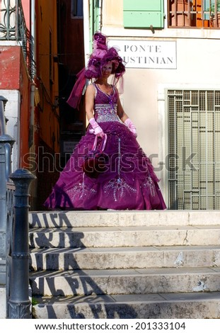 VENICE, ITALY - FEBRUARY 24: The carnival of Venice is held in Italy. Beautiful woman in colorful costume and mask on one of Venetian bridges. Wonder and Fantasy Nature. Venice, Italy - Feb 24, 2014