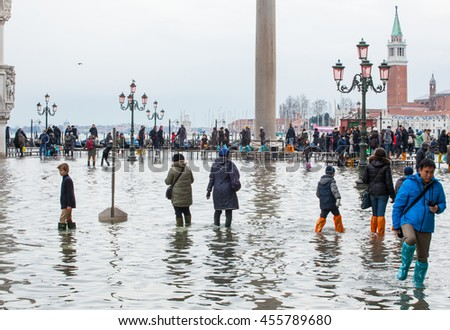 Venice, Italy - February 01, 2015: Tourists in San Marco square with high tide. It's a phenomenon which occurs in winter time. This can cause of a large inflow of water into the Venetian Lagoon.