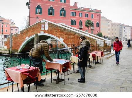 VENICE, ITALY - FEBRUARY 13, 2015: Tourists looking at map during Carnival (woman holding masks). The Carnival in Venice is annual event which ends on Shrove Tuesday. - stock photo
