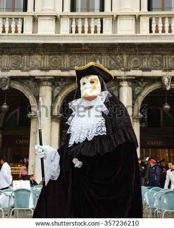 VENICE, ITALY - FEBRUARY 14, 2015: Traditional Venetian mask in St Mark's Square during the Carnival. The Carnival in Venice is annual event which ends on Shrove Tuesday. - stock photo