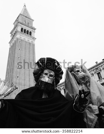 VENICE, ITALY - FEBRUARY 14, 2015:Two masks in St Mark's Square square during the traditional Carnival. The Carnival in Venice is annual event which ends on Shrove Tuesday. - stock photo