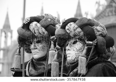 VENICE, ITALY - FEBRUARY 16, 2015:Two masks in turbans at St Mark's Square  (St Mark's Basilica at background) during traditional Carnival. Carnival is annual event which ends on Shrove Tuesday. - stock photo
