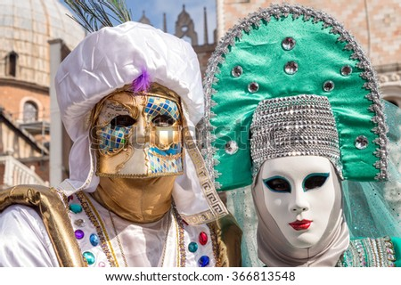 VENICE, ITALY - FEBRUARY 15, 2015: Two models disguised with traditional venetian costumes, posing in San Marco square during the Carnival of Venice, in Italy. - stock photo