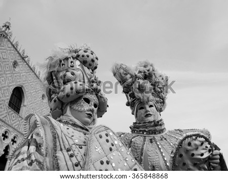 VENICE, ITALY - FEBRUARY 15, 2015: Two noble masks near Doge's Palace in St Mark's Square during traditional Carnival. The Carnival in Venice is annual event which ends on Shrove Tuesday. - stock photo