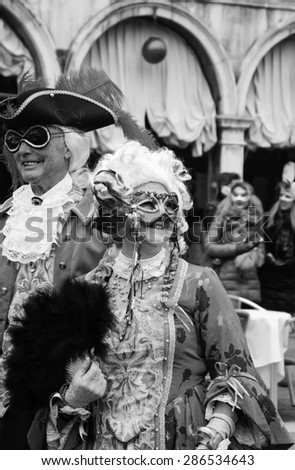 VENICE, ITALY - FEBRUARY 14, 2015:Two seniors in masks at St Mark's Square during traditional Carnival. The Carnival in Venice is annual event which ends on Shrove Tuesday.